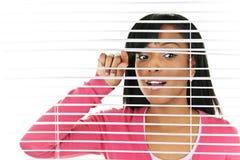 Mulher que olha através das cortinas venetian Fotografia de Stock Royalty Free
