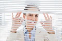 Mulher que olha através de algumas cortinas Imagem de Stock