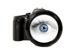 Mulher que olha através de uma lente de câmera Fotografia de Stock