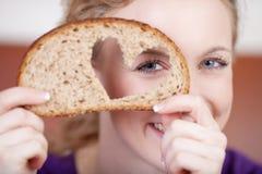 Mulher que olha através do furo dado forma coração no pão Fotografia de Stock