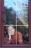 Mulher que olha através do indicador Imagens de Stock Royalty Free