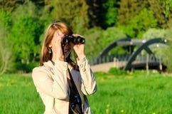 Mulher que olha através dos binóculos Imagem de Stock Royalty Free