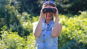Mulher que olha através dos binóculos Turista da menina com uma trouxa outdoor filme