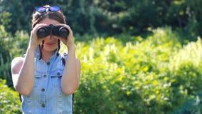 Mulher que olha através dos binóculos Turista da menina com uma trouxa outdoor video estoque