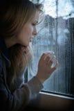 Mulher que olha através da janela com pingos de chuva Fotografia de Stock Royalty Free
