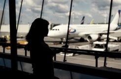 Mulher que olha através da janela no aeroporto Foto tonificada Imagens de Stock