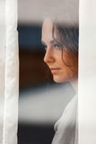 Mulher que olha através do indicador Fotos de Stock Royalty Free