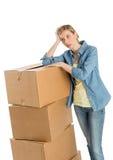 Mulher que olha ausente ao inclinar-se em caixas de cartão empilhadas foto de stock