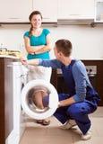 Mulher que olha como o trabalhador novo que repara a máquina de lavar Fotos de Stock