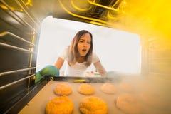 Mulher que olha cookies queimadas no forno Fotos de Stock