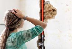 Mulher que olha dano após um escape da tubulação de água foto de stock
