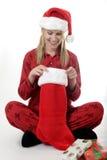 Mulher que olha em sua meia do Natal Fotografia de Stock