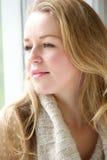 Mulher que olha fixamente fora através da janela Fotografia de Stock Royalty Free