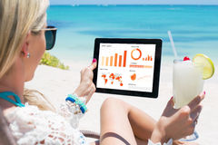 Mulher que olha gráficos e cartas na tabuleta digital fotos de stock royalty free