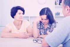 Mulher que olha infeliz ao falar com pais superiores fotografia de stock royalty free