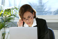 Mulher que olha irritada com seu computador Fotografia de Stock Royalty Free