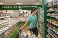 Mulher que olha a lista de compra no supermercado, Pequim foto de stock royalty free