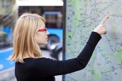 Mulher que olha na placa do mapa do metro imagem de stock