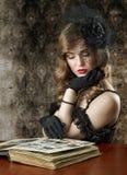 Mulher que olha no álbum de fotografias velho Foto de Stock