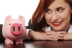 Mulher que olha no banco piggy cor-de-rosa Fotografia de Stock