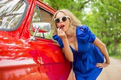 Mulher que olha no espelho lateral dos carros e que põe sobre o batom Imagem de Stock Royalty Free