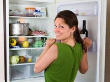 Mulher que olha no refrigerador Fotografia de Stock Royalty Free