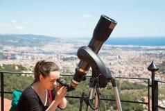 Mulher que olha no telescópio Imagem de Stock
