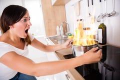 Mulher que olha o alimento queimado em cozinhar o potenciômetro imagem de stock royalty free