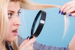 Mulher que olha o cabelo atrav?s da lupa imagens de stock royalty free
