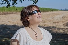 Mulher que olha o eclipse solar com vidros do eclipse fotografia de stock