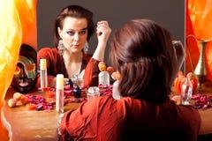A mulher que olha o espelho e que põr compo Fotografia de Stock Royalty Free