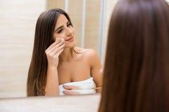 Mulher que olha o espelho em casa e que aplica o creme em sua cara Foto de Stock Royalty Free