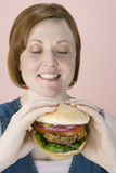 Mulher que olha o Hamburger Fotos de Stock Royalty Free