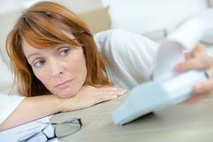 Mulher que olha o impresso na calculadora forçada foto de stock