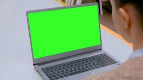 Mulher que olha o laptop com a tela verde vazia no caf? filme
