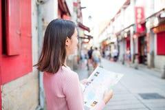 Mulher que olha o mapa da cidade em Rua a Dinamarca Felicidade da cidade de Macau Foto de Stock Royalty Free