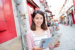 Mulher que olha o mapa da cidade na cidade de Macau Imagens de Stock