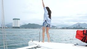 Mulher que olha o mar, mãos da elevação e dançando ao apreciar um cruzeiro no iate vídeos de arquivo