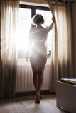 Mulher que olha o nascer do sol através da janela Foto de Stock Royalty Free