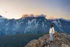 Mulher que olha o nascer do sol impressionante sobre vales, cumes e picos de montanha Opinião de ângulo larga de 3000 m no ` Aost fotografia de stock royalty free