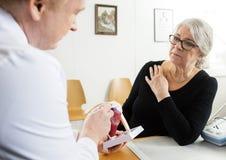 Mulher que olha o punho masculino Mo do doutor Explaining Shoulder Rotator imagem de stock