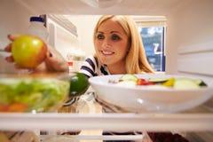Mulher que olha o refrigerador interno completamente do alimento e que escolhe Apple foto de stock