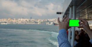 A mulher que olha o smartphone horizontal com tela verde toma imagens Feche acima do tiro das mãos do ` s da mulher com móbil Ist imagens de stock royalty free