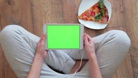 Mulher que olha o tablet pc com a tela verde na casa video estoque