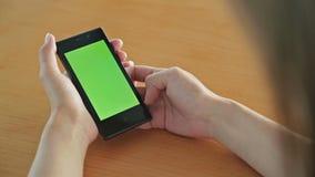 Mulher que olha o tablet pc com a tela verde no café filme