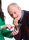 Mulher que olha o telefone esperto com o homem surpreendido e surpreendido imagens de stock