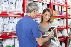 Mulher que olha o vendedor Using Digital Tablet na loja do animal de estimação fotos de stock royalty free