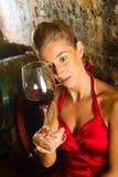 Mulher que olha o vidro de vinho na adega Fotos de Stock Royalty Free