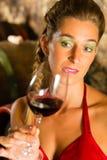 Mulher que olha o vidro de vinho tinto na adega Imagem de Stock