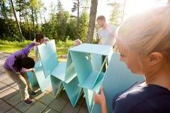 Mulher que olha os amigos que fazem a pirâmide de pranchas de madeira Fotos de Stock
